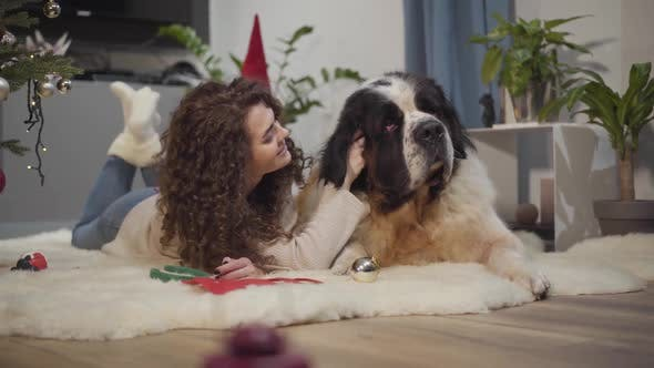 Thumbnail for Portrait of Charming Caucasian Girl with Long Curly Hair Caressing Her Big Dog Behind Ear. Happy
