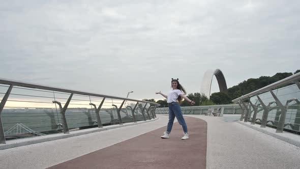 Happy Teen Girl Performing Stylish Dance on Bridge