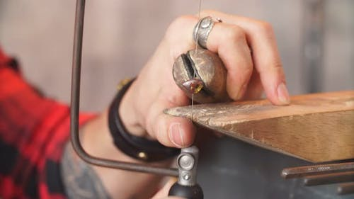 Serious Man Testing the New Fret Saw. High-grade Steel for Repairing Adornment