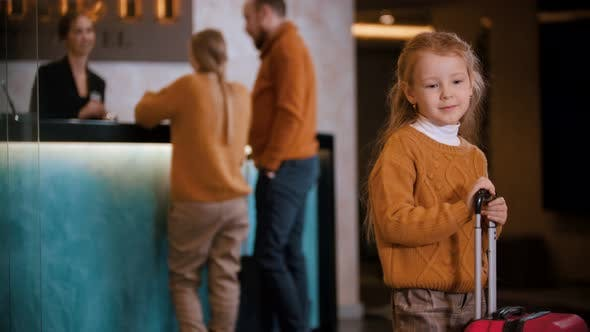 Thumbnail for A Family Checking in the Luxury Hotel - a Little Girl Standing with a Suitcase and Waiting for Her