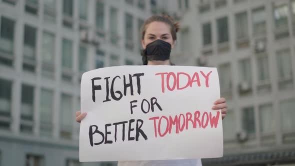 Thumbnail for Rack-Fokus ändert sich vom ernsten Gesicht des Aktivisten zu Banner mit Slogan. Ernsthafte schöne kaukasische