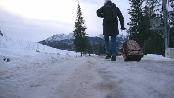Thumbnail for Low View of Unrecognizable Man Walks on Trail and Pulling Suitcase on Wheels During Winter Day