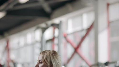 Довольно Sportswoman на корточках со штангой в бодибилдинг обучение в тренажерный зал