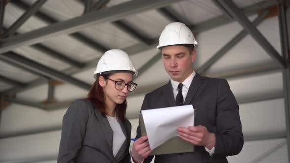 Young Man and Woman in Helmets with Documents at a Construction Site. Businessmen in Suits Conclude