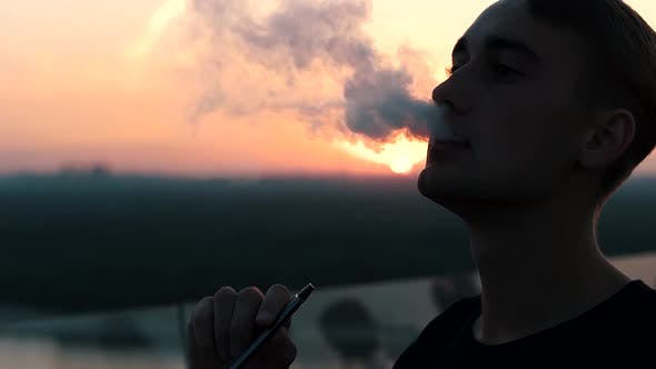 Thumbnail for Guy Smokes an Electronic Cigarette