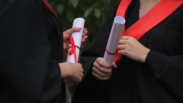 Thumbnail for Female Graduates in Academic Dresses Holding Diplomas and Talking About Future
