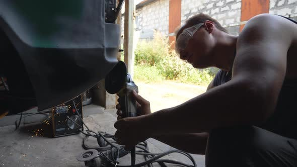 Mechanic Wearing Protective Glasses Polishing Auto with Electric Tool in Garage