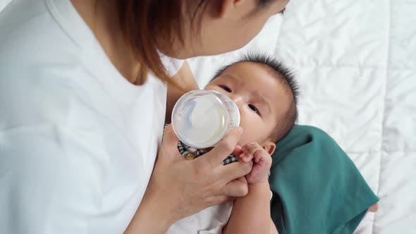 mother feeding milk from bottle and baby sleeping on a bed