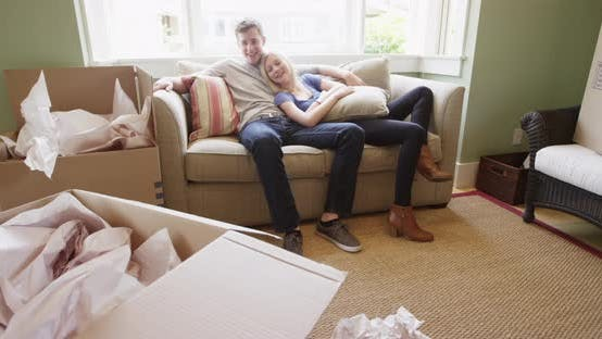 Thumbnail for Young couple relaxing on couch after unpacking into new apartment