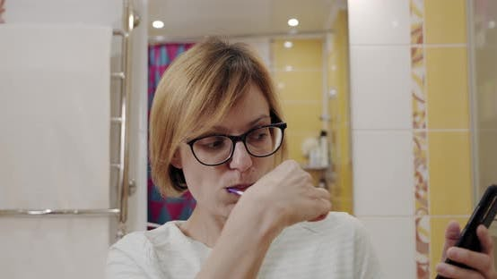 Thumbnail for Close Up Beautiful Carefree Woman Cleaning Her Teeth with Toothbrush and Browsing Apps on Her