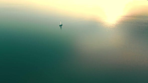Thumbnail for Aerial View One Yacht at Sunset in the Open Sea. Flight at Sunset Near the Yacht with a Sail View