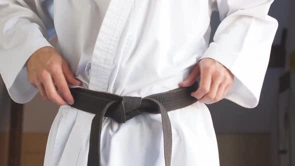Thumbnail for Hands Tightening Black Belt on Man Dressed in Kimono