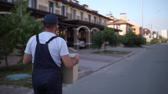 Thumbnail for Delivery Man Walking Along Townhouses with Box