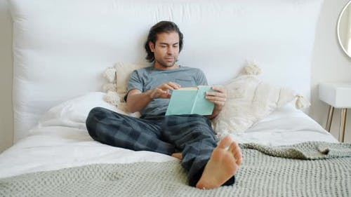Slow Motion of Intelligent Guy Reading Book Enjoying Story in Bed at Home