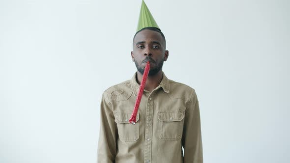 Slow Motion Portrait of African American Man Wearing Bright Hat Blowing Party Horn with Miserable