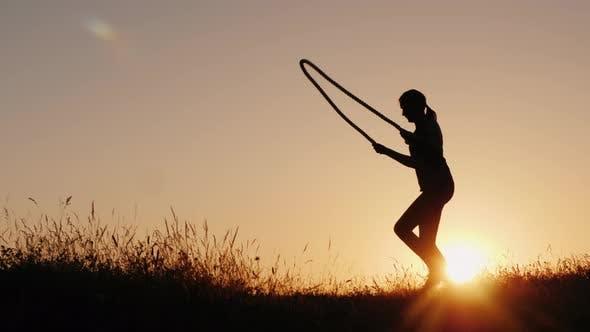 Thumbnail for Silhouette of a Woman - Jumping Through the Rope at Sunset