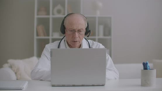 Thumbnail for Male Doctor Is Consulting Online Colleagues and Patients, Elderly Male Therapist Is Sitting at