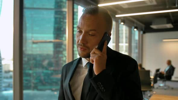 Portrait of Attractive Caonfident Businessman in Coworking Office Calling To His Deal Partner