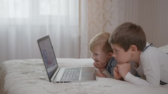 Thumbnail for Cute Small Child Boy Using Educational Application on Computer Sitting on Couch with Smaller Smiling
