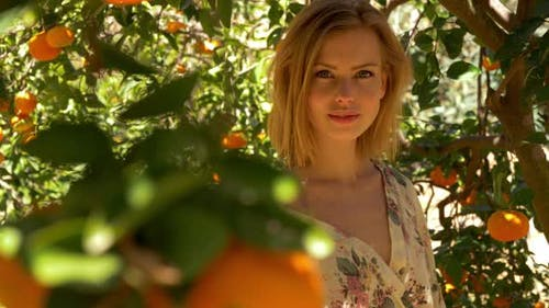 Beautiful Model with Blonde Hair under Orange Trees Posing for the Camera