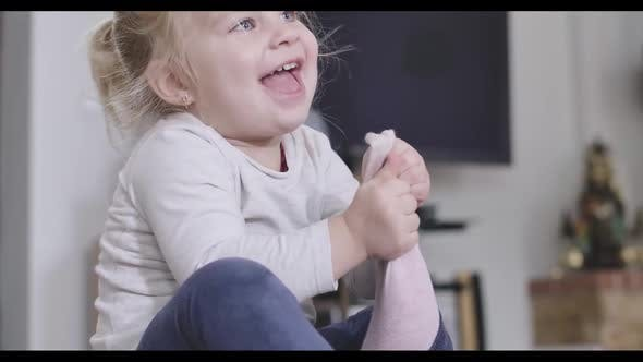 Thumbnail for Close-up Portrait of Positive Little Girl Taking Off Pink Sock. Blond Caucasian Child Enjoying Free