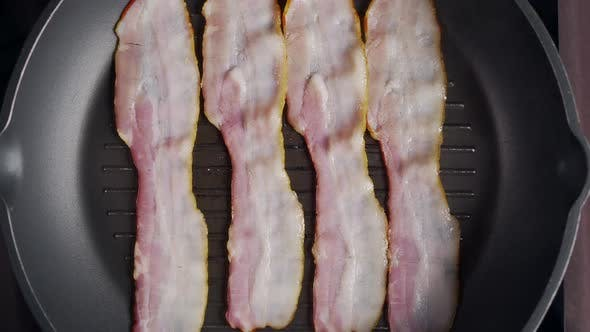 Thumbnail for Flat Lay Shot of Pieces of Bacon Being Roasted on the Hot Grill Pan, Slow Motion Shot of Grilled