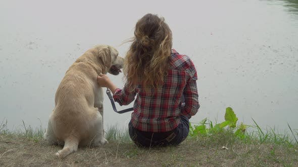 Thumbnail for Curly Woman and Labrador Is Sitting Near the River