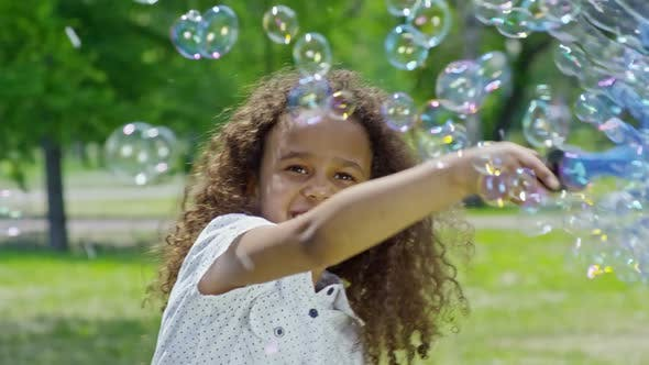 Thumbnail for Playful Little African Girl Making Bubbles in Park