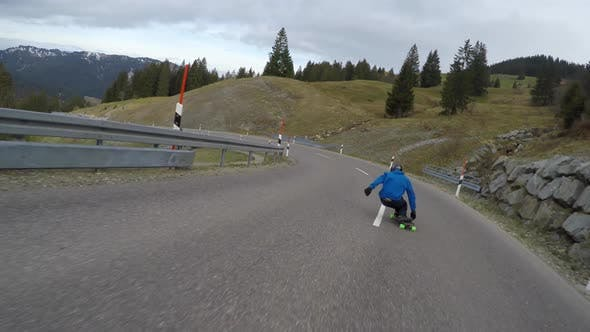 Thumbnail for A skateboarder downhill skateboarding on a mountain highway road
