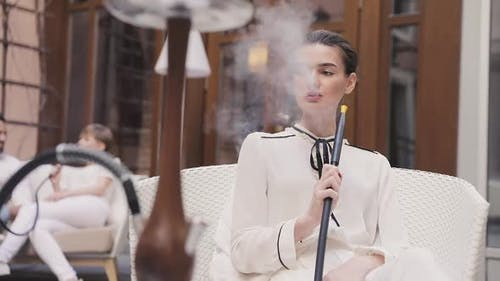 Shisha Bar. Beautiful Woman Smoking Hookah At Restaurant Lounge