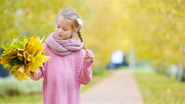 Thumbnail for Portrait of Adorable Little Girl with Yellow and Orange Leaves Bouquet Outdoors at Beautiful Autumn