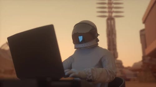 Astronaut in the Space Suit Works on a Laptop in a Space Colony on One of the Planets
