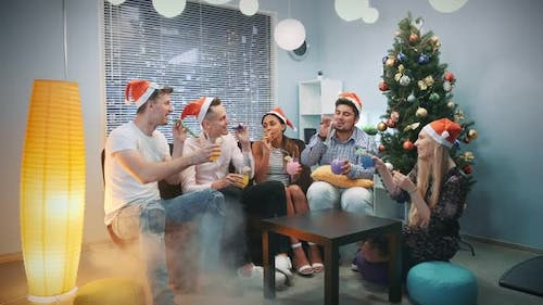 Multi-ethnic Company in Santa Hats Blowing Party Whistle and Making Cheers in Smoke