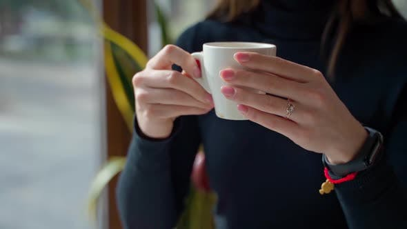 Thumbnail for White cup with coffee in woman's hands