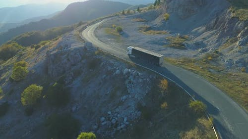 Aerial View Of Cargo Lorry Driving on Mountain Road at Sunrise