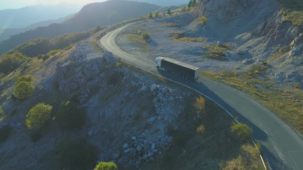 Thumbnail for Aerial View Of Cargo Lorry Driving on Mountain Road at Sunrise
