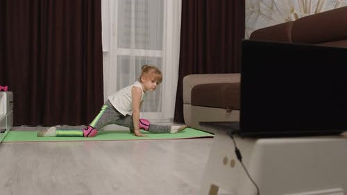 Children Girl Watching Online Distance Lessons with Trainer on Laptop Exercising Twine at Home