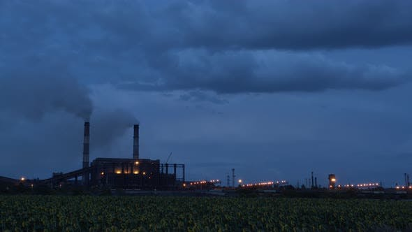 Thumbnail for Timelapse of Clouds of Smoke Billowing From Smokestacks Into the Twighlight Sky, .