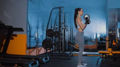 Girl Lifts the Barbell in the Gym