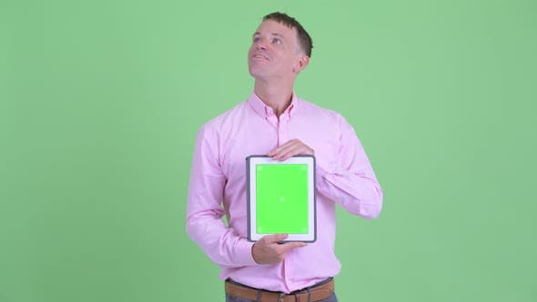 Thumbnail for Happy Businessman Thinking While Showing Digital Tablet