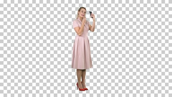 Woman Applying Lipstick Looking at Her Phone, Alpha Channel