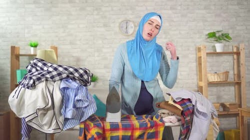 Tired Young Muslim Woman Is Engaged Ironing Pile Laundry