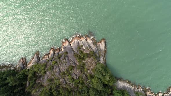 Thumbnail for Aerial Looking Down On Mellow Waves Of Turquoise Ocean Water On Rocky Shore