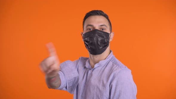 Thumbnail for Young Man Showing Stop Sign. Man in Face Mask Showing Stop Sign with Crossed Hands, Waving Finger