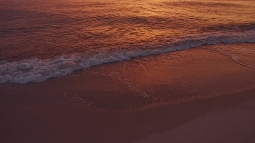 Sea surf against the background of an orange sunset