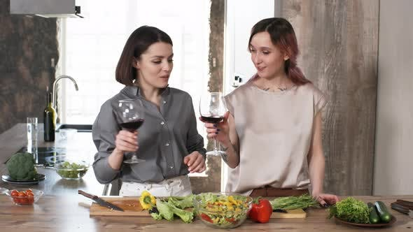 Cover Image for Two Young Women Drinking Wine and Cooking Salad in Kitchen