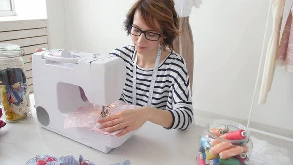 Young Dressmaker Woman Sews Clothes