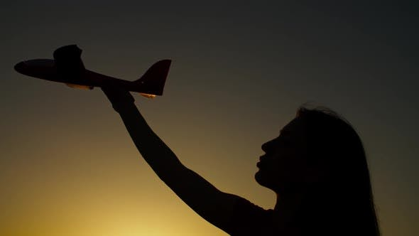 Thumbnail for Silhouette of Female Hand with Toy Airplane at Sunset