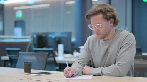 Junger Geschäftsmann versucht auf Papier zu schreiben Scheitern