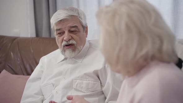 Thumbnail for Close-up Portrait of Old Caucasian Grey-haired Man Talking with Wife at Home, Married Retirees